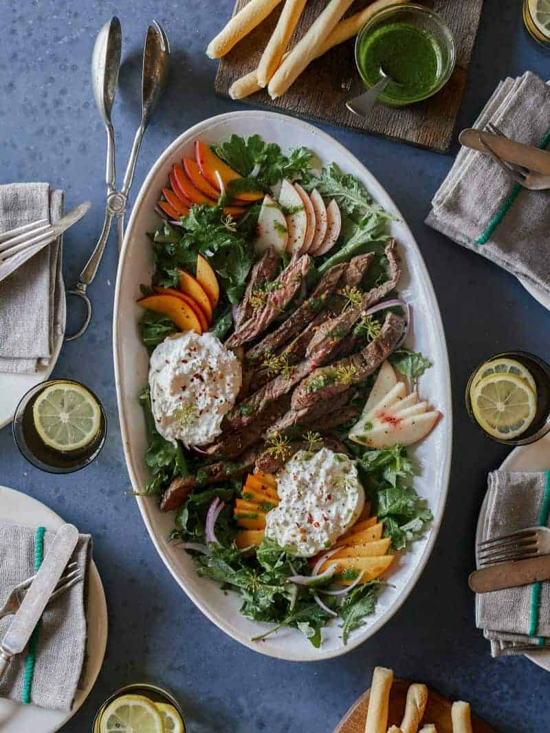 A platter of grilled skirt steak with fresh peaches and burrata.