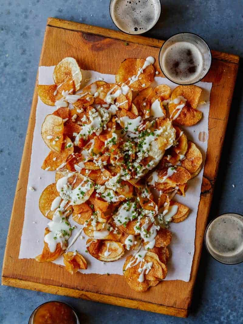 Homemade potato chips drizzled in gorgonzola cheese sauce on a wooden cutting board next to drinks.