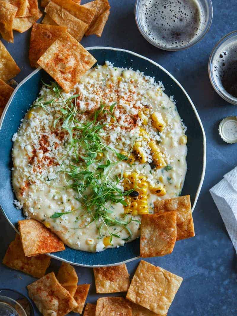 Elote queso dip in a bowl served with homemade tortilla chips.