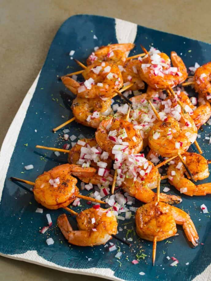 A platter of smoked paprika and garlic shrimp skewers topped with onion.