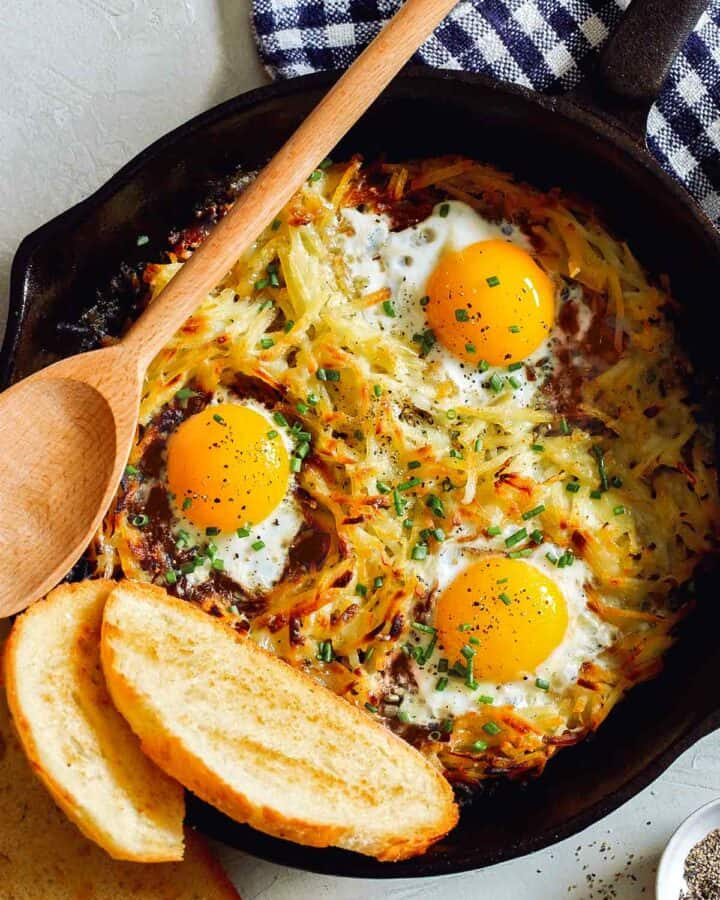 Simple cheesy skillet hash browns and eggs with bread and a wooden spoon.