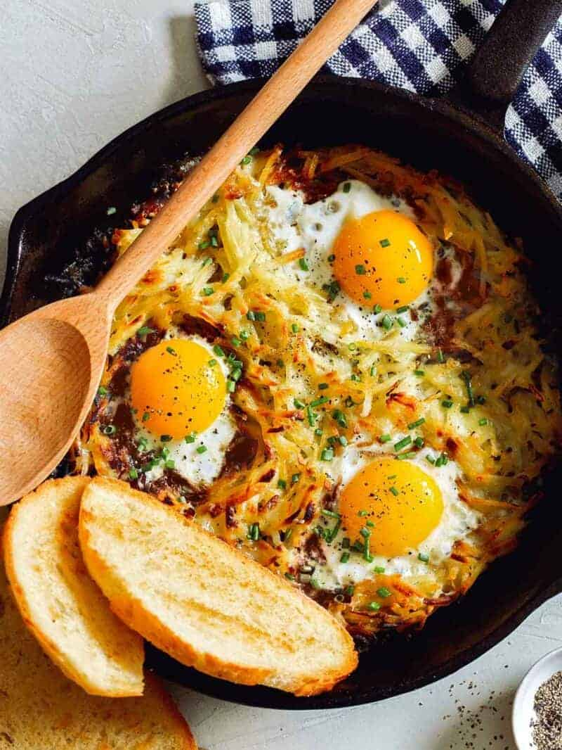 Eggs and hash browns made in a skillet with toast on the side.