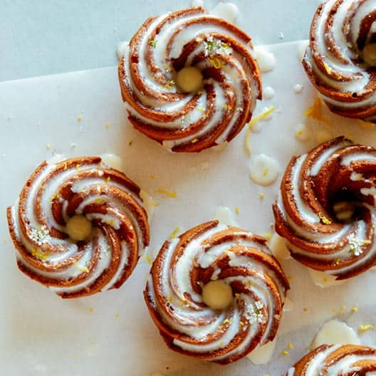 A half dozen mini citrus bunt cakes with lemon glaze.