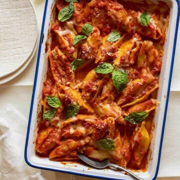 Turkey sausage and mascarpone stuffed shells in a baking dish with a spoon.