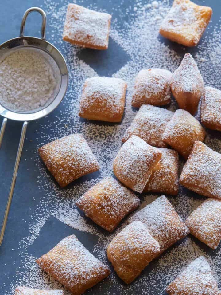 Chai spiced buttermilk beignets covered in powdered sugar with a small sieve.