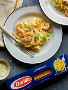 A plate of shrimp linguine with cream sauce next to a box of Barilla linguine.