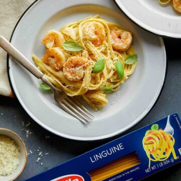 A plate of shrimp linguine with cream sauce next to a box of Barilla linguine.