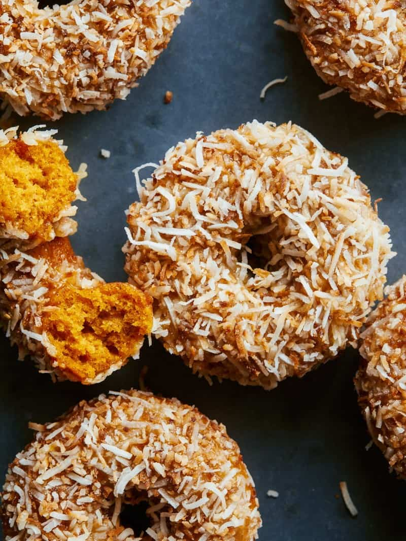 A close up of baked pumpkin cake doughnuts with maple glaze and toasted coconut.