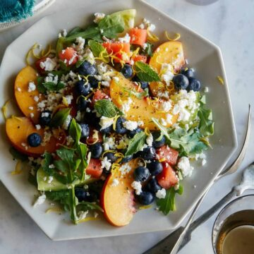 A plate of end of summer fruit salad with forks.