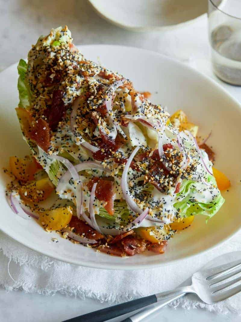 Everything seasoning wedge salad with a fork and drink.