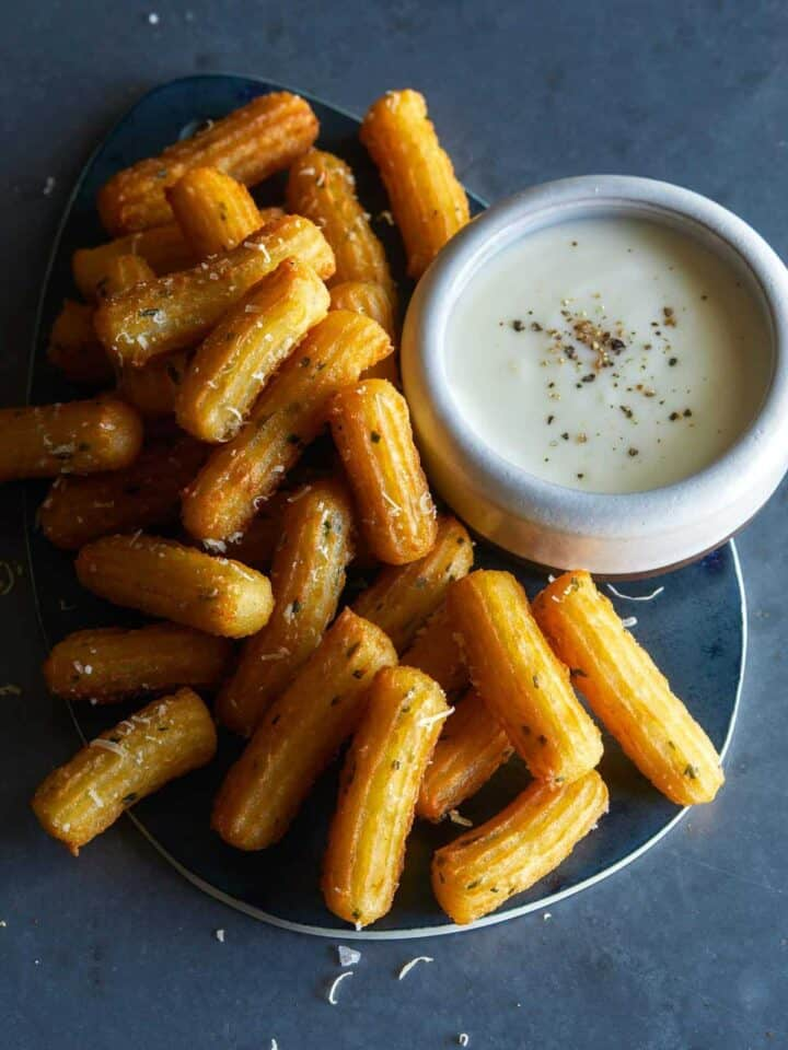 A plate of savory herb churros with white queso dip on the side.