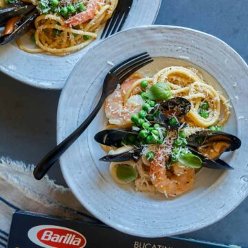 A plate of seafood carbonara with a fork and a box of Barilla Collezione Bucatini.