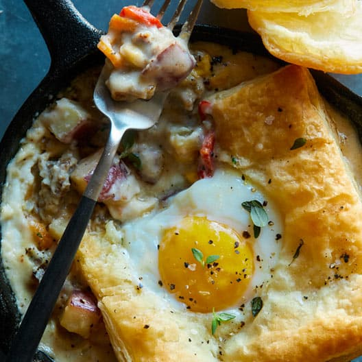 Close up on a breakfast pot pie in an individual skillet.