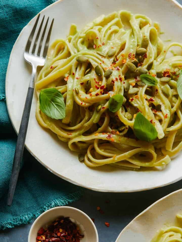 A close up of fettuccine with creamy avocado garlic sauce in a bowl with a fork.