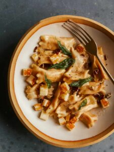 Creamy sweet potato agnolotti on a plate with a fork.