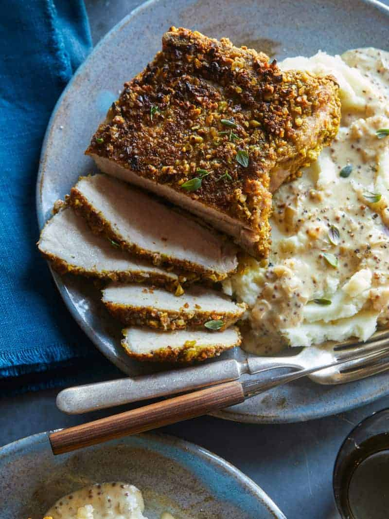 A close up of sliced pistachio crusted pork chop with mashed potatoes, a fork and knife.