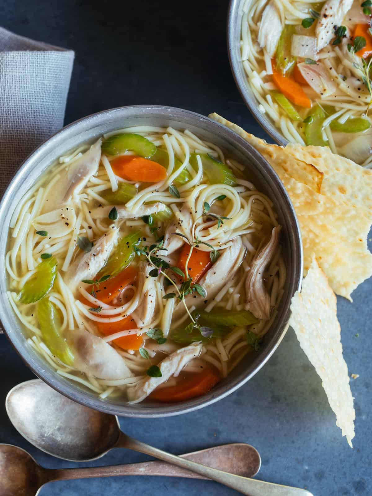 Bowls of chicken noodle soup with a spoon.