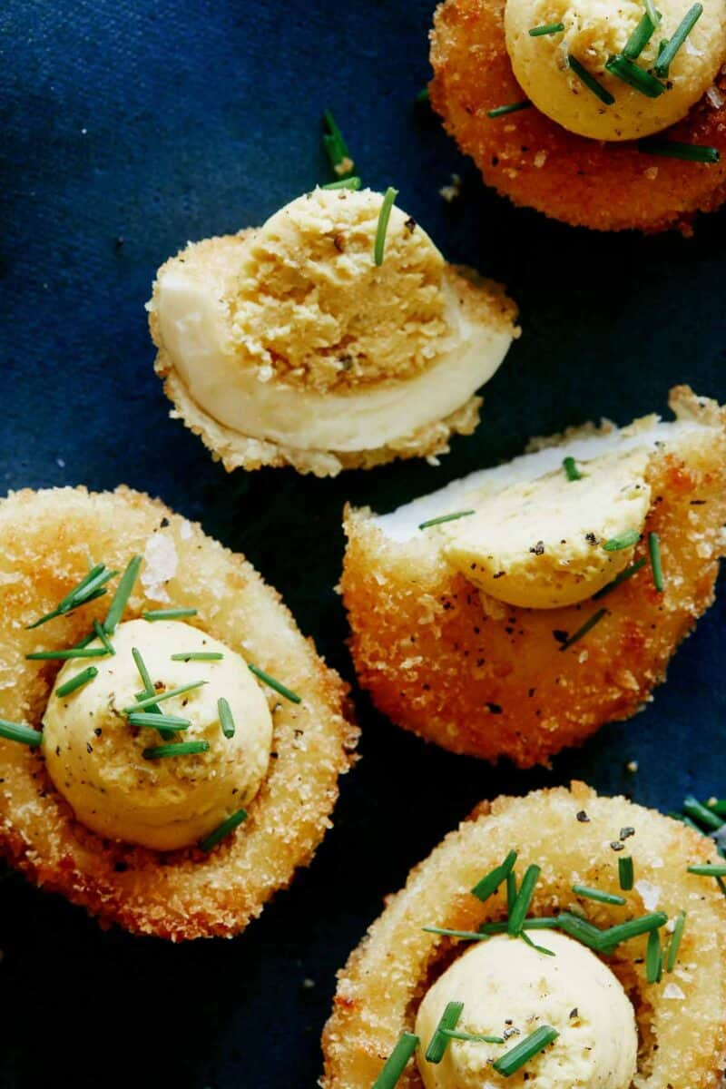 A close up of fried deviled eggs with one cut in half.