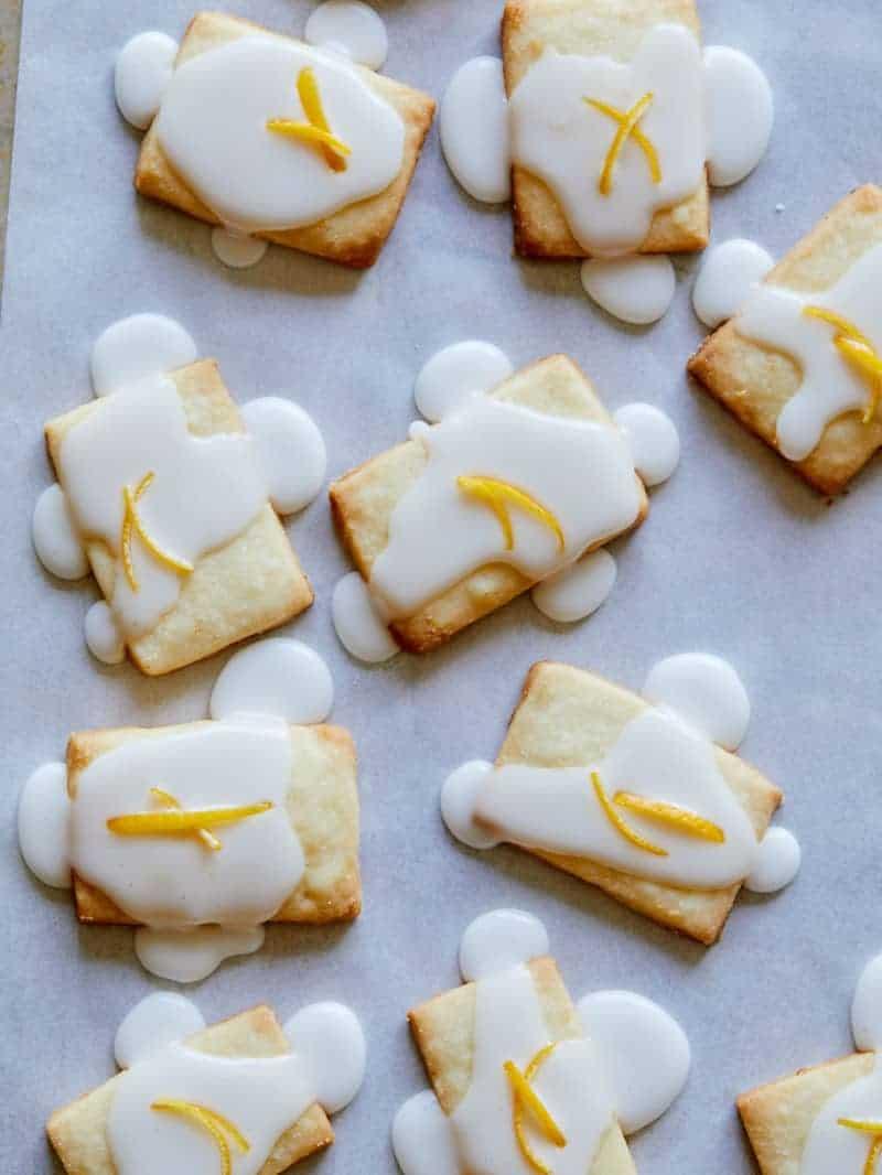 Meyer Lemon Meltaways on a baking sheet freshly glazed with frosting.