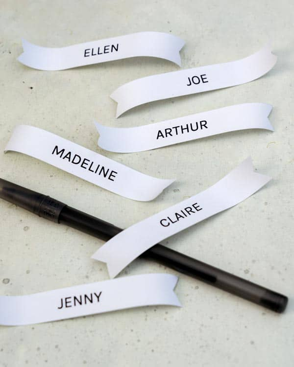 Curling the edges of name tags with a pen.