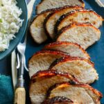 A platter of sliced char siu pork tenderloin next to white rice and a carving fork.