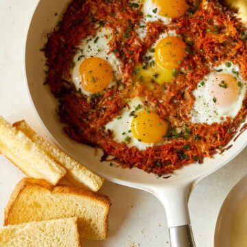 Cheesy skillet sweet potato hash browns and eggs with toast.