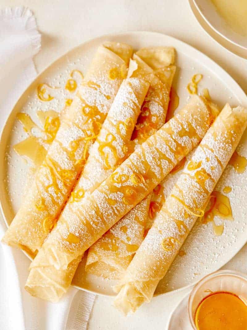 Freshly made meyer lemon and ricotta stuffed crepes on a platter for breakfast.