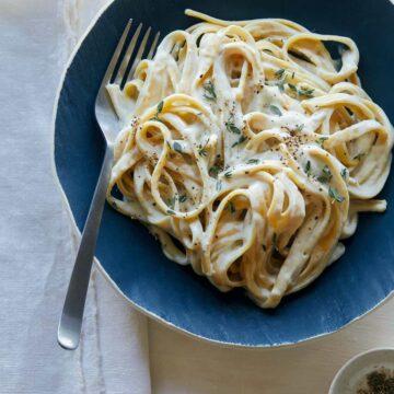 Roasted garlic vegan fettuccine alfredo on a blue plate with a fork.