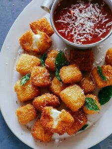 A close up of hallumi nuggets with marinara sauce on the side.