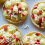 A close up of coconut lime tarts topped with sugar soaked strawberries.