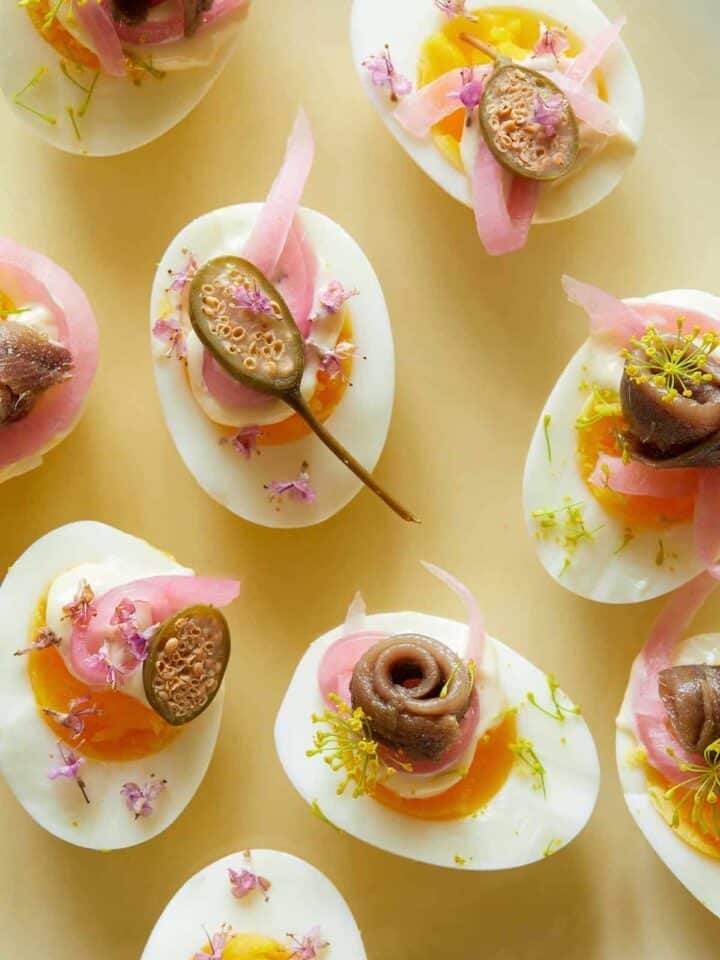 A close up of several undeviled eggs with pickled red onion, caperberries, and anchovies.