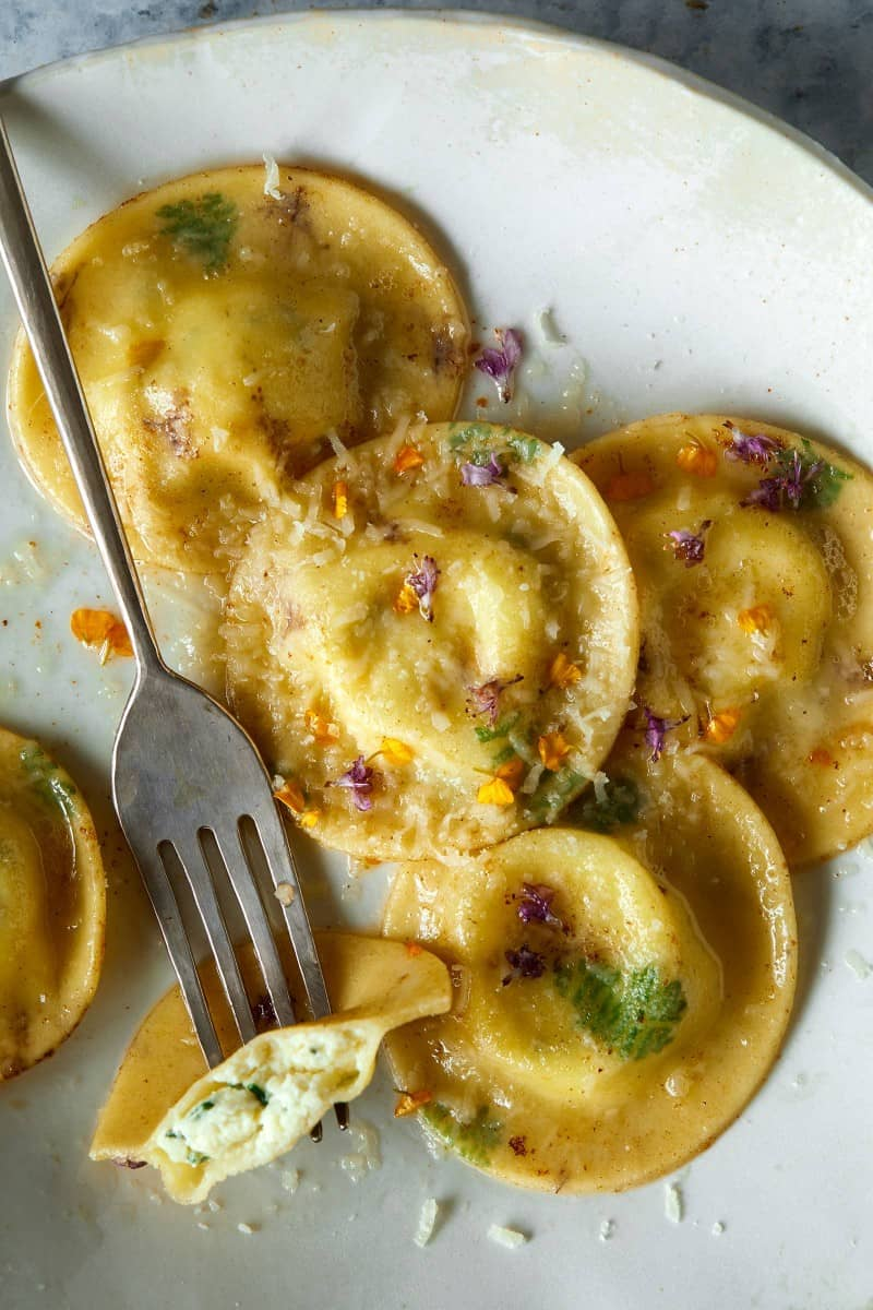 A close up of cooked floral laced ravioli with cheesy herb ricotta filling and a fork.