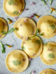Uncooked floral laced ravioli with cheesy herb ricotta filling.