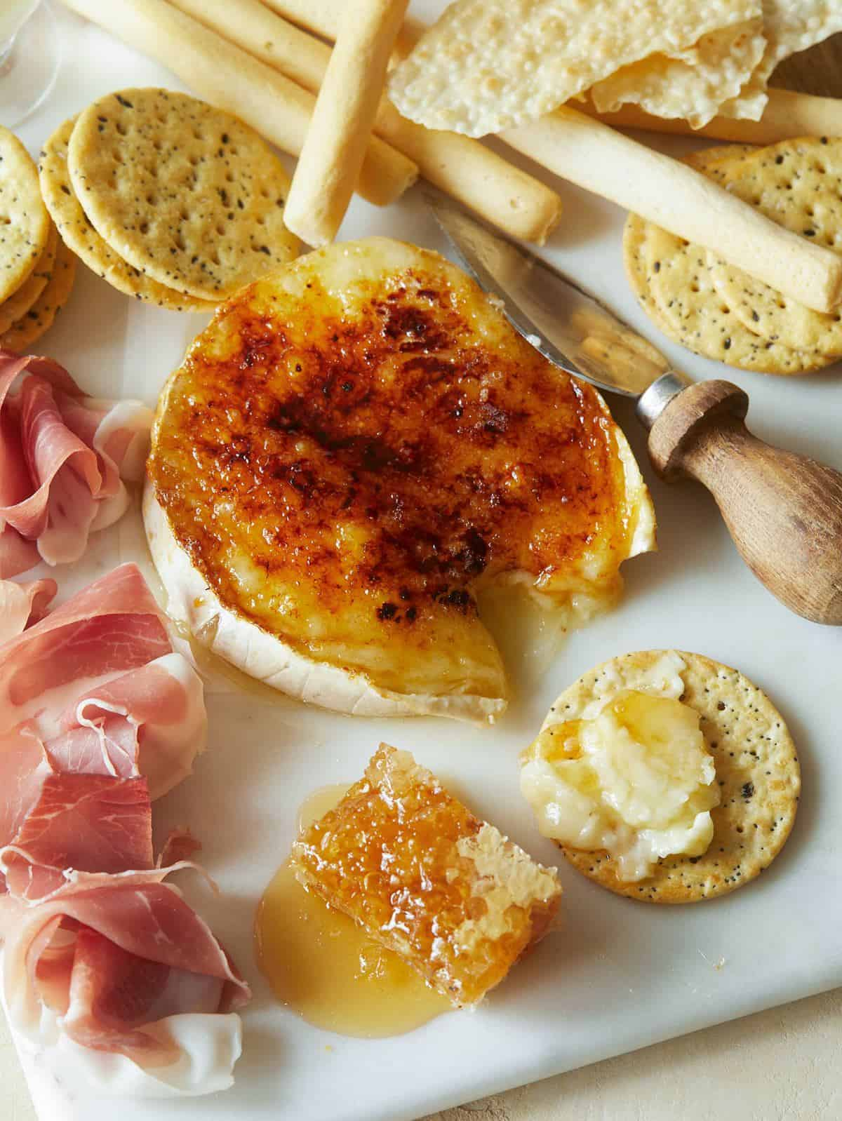 Honey brûlée brie with crackers, meat, and cheese knife.