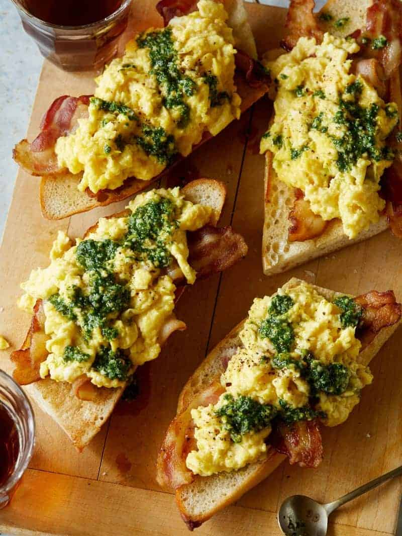 A close up of pesto scrambled eggs with bacon over toast on a wooden cutting board.
