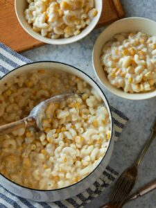 A pot and bowls of creamed corn mac and cheese with a serving spoon.