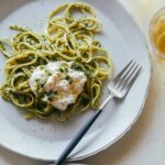 A plate of English pea, basil, and pistachio pesto linguine with burrata and a fork.