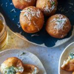 A platter of spinach and artichoke stuffed beignets and servings on small plates.