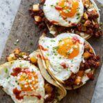 A close up of chorizo and fried egg breakfast tacos.