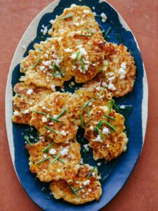 Corn cakes with chives and queso fresco on blue and white platter.