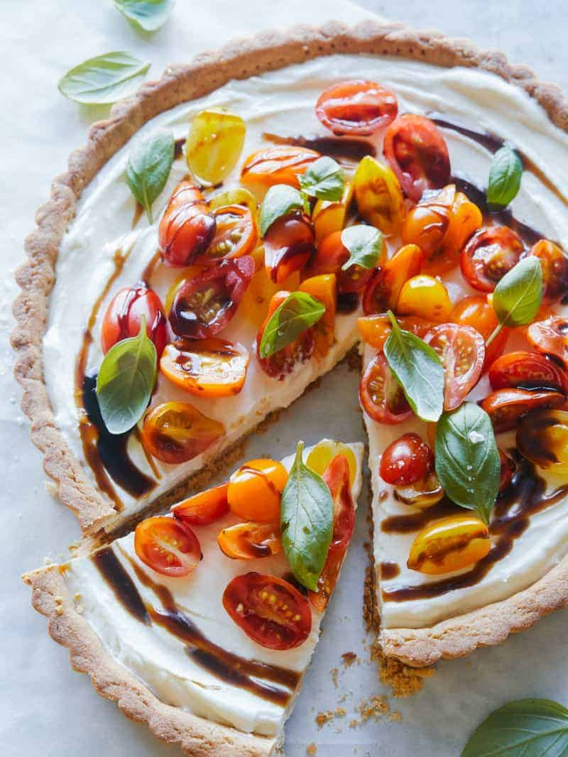 A bruschetta and whipped goat cheese tart with a slice cut out.