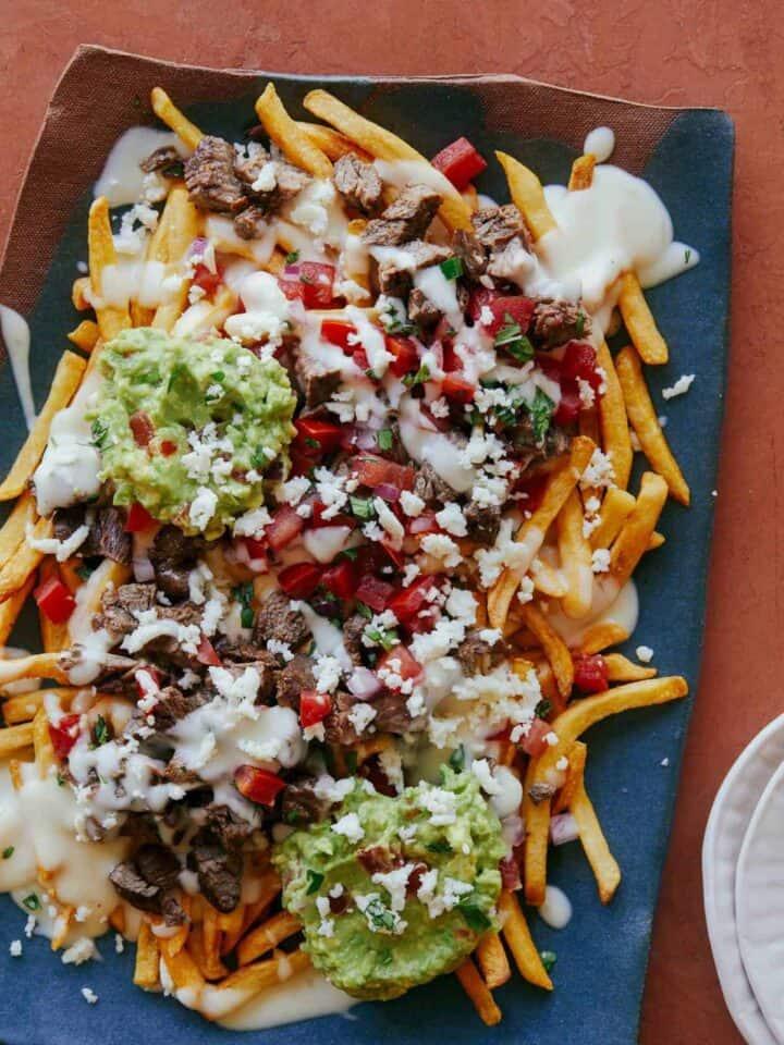 Carne asada fries on a blue platter.