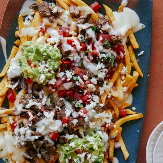Carne Asada fries made on a platter with some plates on the side.