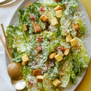 Simple salad with quince, manchego, and marcona almonds with serving spoons.