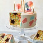 A sliced and partially served 4th of July funfetti cake with candles and flags.