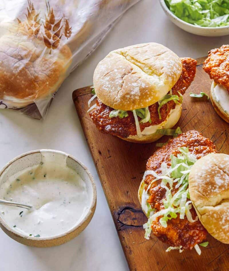 Nashville honey hot chicken sandwiches on a wooden cutting board with sauce on the side.