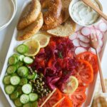 A platter of beet cured salmon, bagels and veggies with wooden serving utensils.