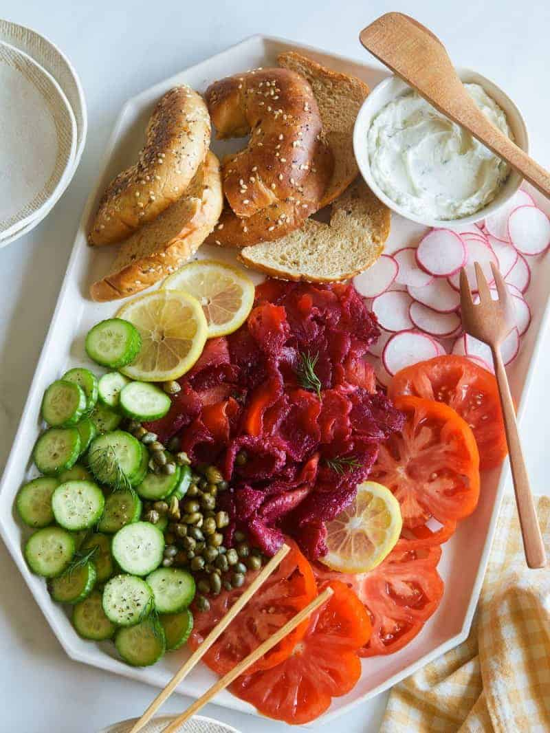 A platter of beet cured salmon with bagels, cream cheese, and veggies.