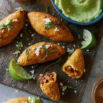 A close up of chorizo molotes with lime wedges and sauce on the side.