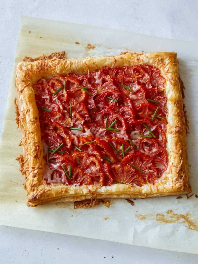 A tomato tart on a sheet of baking parchment ready to be cut and served.